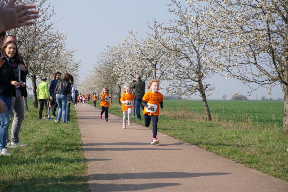 Kinder laufen an jubelnden Zuschauern vorbei